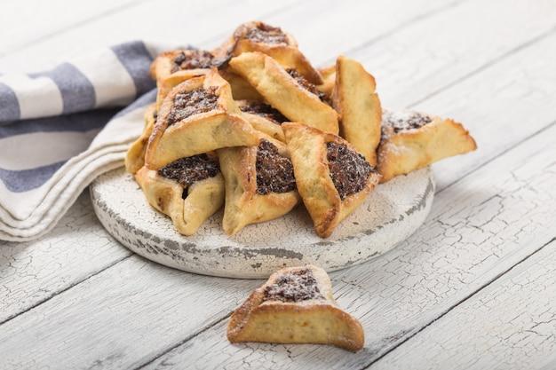 Biscuits hamantaschen juifs traditionnels aux abricots secs, dattes. concept de célébration de pourim. fond de vacances ¡arnival. mise au point sélective. copiez l'espace.