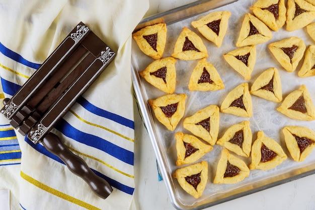 Biscuits juifs hamantaschen avec de la confiture sur une plaque à pâtisserie avec bruiteur pour pourim.