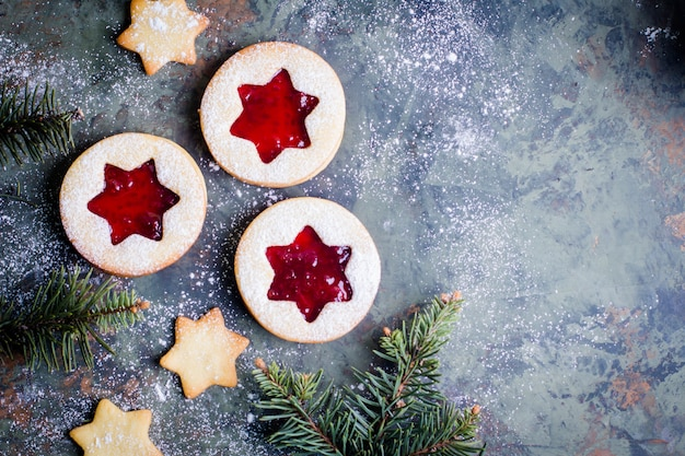 Biscuits linzer de noël avec de la confiture de framboises sur fond de table verte.