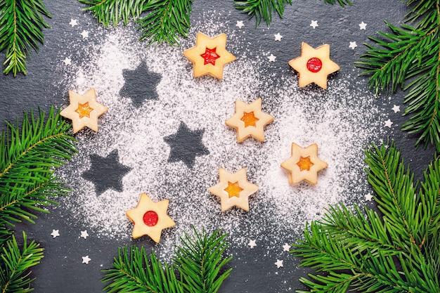 Biscuits linzer de noël avec confiture de framboises sur table en ardoise