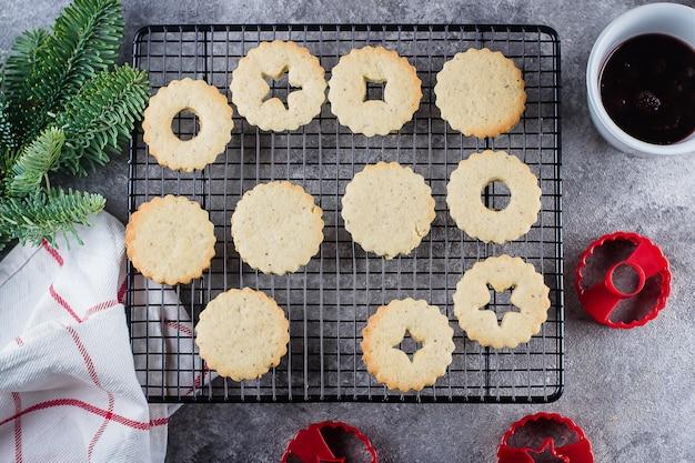 Biscuits linzer de noël avec confiture de fruits rouges sur fond de table en béton gris