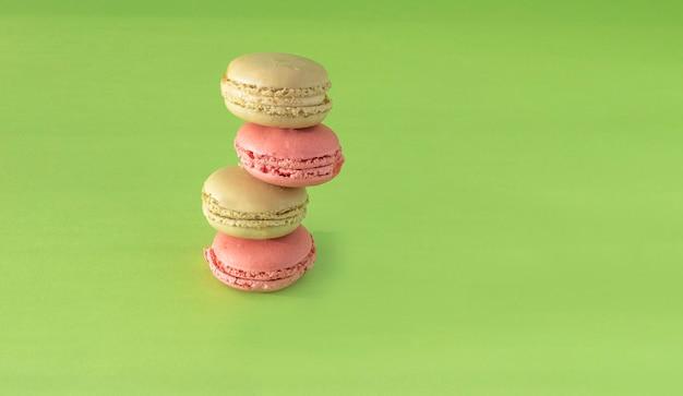 Biscuits macaron pistache verte et framboise rose disposés en composition verticale sur fond vert.