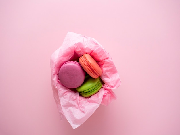 Les biscuits macaron se trouvent dans un panier sur fond rose. vue de dessus, plat, dessert délicieux et sucré