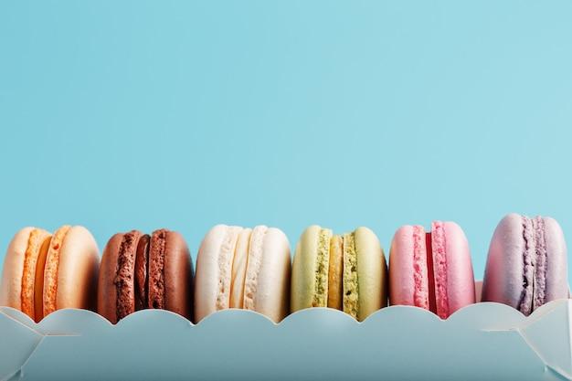 Biscuits macaroni de différentes couleurs dans une boîte blanche sur fond bleu.