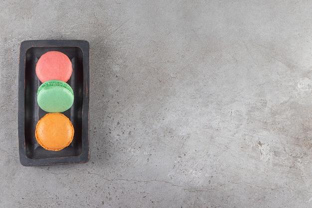 Biscuits macaroni de différentes couleurs dans une planche de bois sombre.