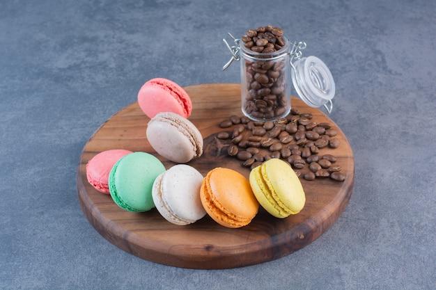 Biscuits macaronis de différentes couleurs avec des grains de café placés sur une planche de bois.