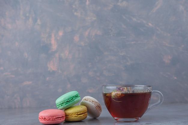 Biscuits macaronis de différentes couleurs avec une tasse en verre de tisane.