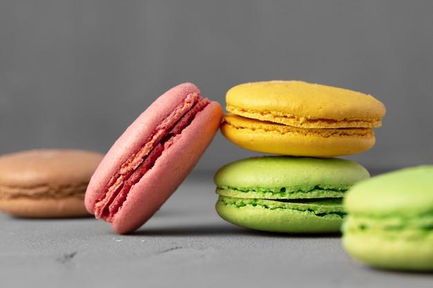 Biscuits macarons colorés sur une surface gris foncé