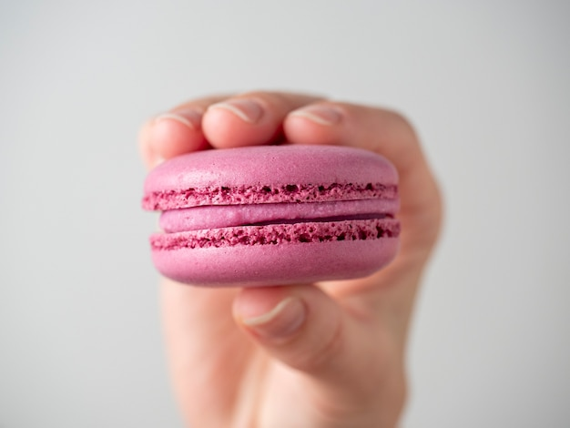 Biscuits macarons sucrés violets à la main sur fond blanc. gros plan, produit de climatisation