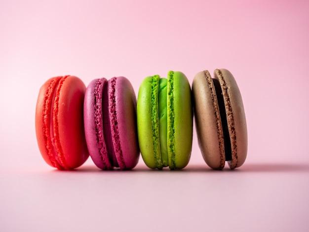 Biscuits macarons traditionnels de différentes couleurs sur fond rose. article isolé, bonbons, confiseries. vue de côté