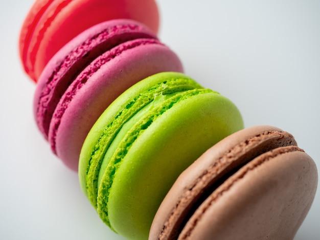 Des biscuits macarons traditionnels de différentes couleurs se trouvent sur un fond blanc. article isolé, bonbons, confiseries. gros plan, vue latérale