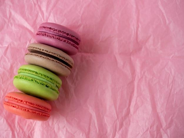 Des biscuits macarons traditionnels de différentes couleurs se trouvent sur un fond de papier rose. article isolé, bonbons, confiseries. vue de dessus, copiez l'espace.