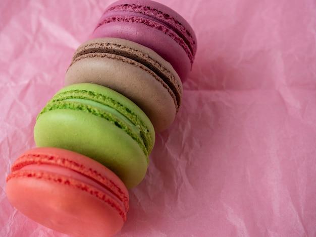 Des biscuits macarons traditionnels de différentes couleurs se trouvent sur un fond de papier rose. article isolé, bonbons, confiseries. vue de dessus