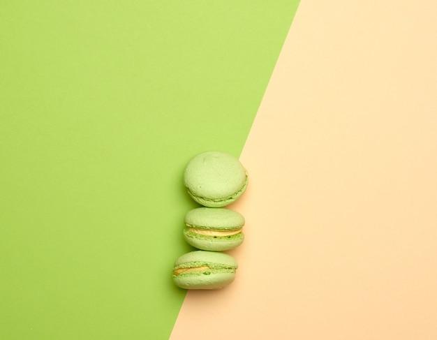 Biscuits macarons verts cuits au four se trouvent dans une rangée sur un fond beige vert