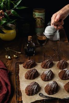 Biscuits madeleine au chocolat boulangerie maison sur une grille de refroidissement avec des ingrédients et des ustensiles sur bois rustique