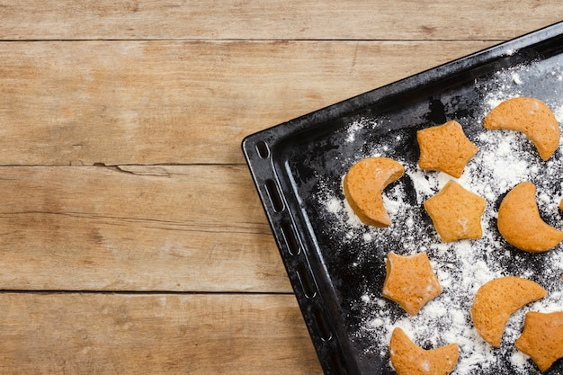 Biscuits à la main sur une plaque à pâtisserie sur une surface en bois. mise à plat, vue de dessus.