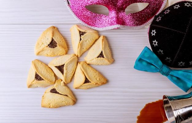 Biscuits maison faits de hamantaschen purim juif avec masque de purim et vin kasher rouge de kippa de purim