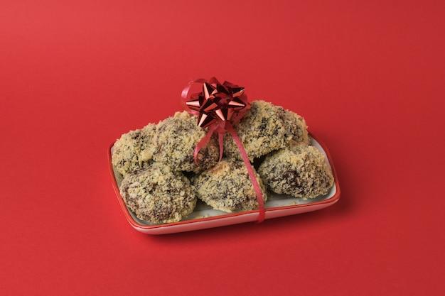 Biscuits maison friables attachés avec un ruban rouge sur rouge