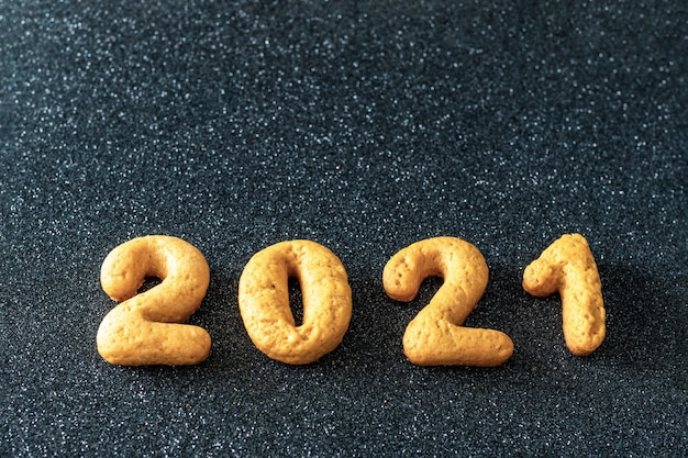 Biscuits maison sous forme de numéros 2021 sur fond noir. fond de nourriture de noël