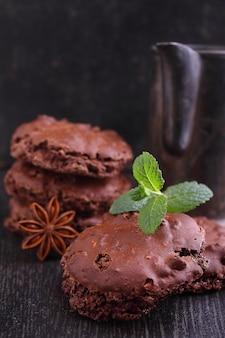 Biscuits de meringue au chocolat avec des noix sur un fond noir