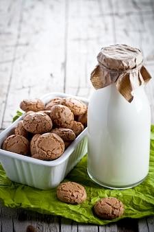 Biscuits à la meringue aux amandes dans un bol et une bouteille de lait