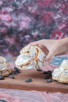 Biscuits de meringue blanche aux raisins secs noirs sur une planche de bois.