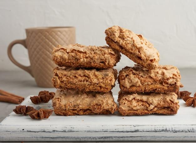 Biscuits meringués cracovie au four sur une planche de bois et tasse en céramique
