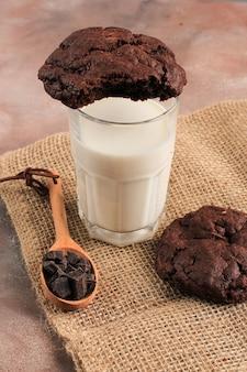 Biscuits moelleux aux pépites de chocolat noir servis avec un verre de lait. copiez l'espace pour la recette, le texte ou la publicité