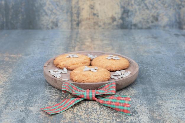 Biscuits de noël aux graines sur une plaque en bois décorée de ruban. photo de haute qualité