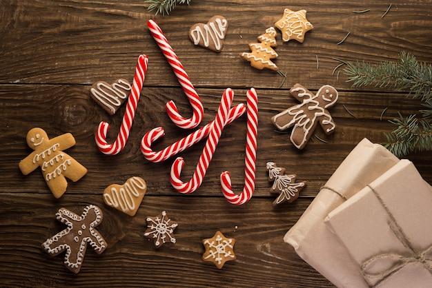 Biscuits de noël et cannes de bonbon sur fond de bois. humeur de vacances. pin. vue de dessus.
