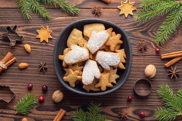 Biscuits de noël dans un bol en argile noire et épices et branches de sapin sur table en bois