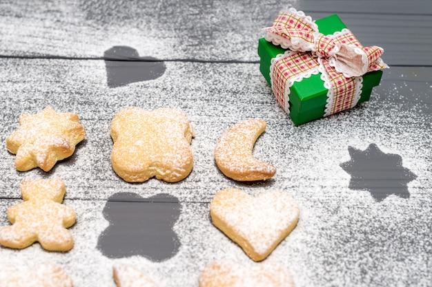 Biscuits de noël de différentes formes avec du sucre en poudre et boîte-cadeau sur table en bois