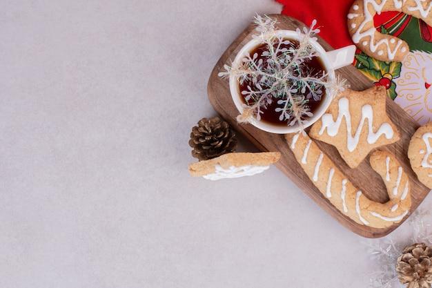 Biscuits de noël avec du thé aromatique en tasse sur une surface blanche
