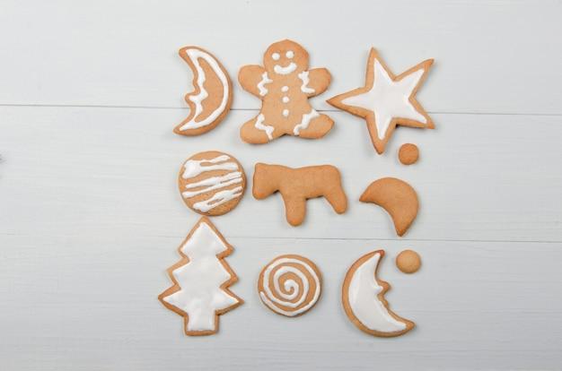 Biscuits de noël faits maison avec glaçage sur table en bois blanc