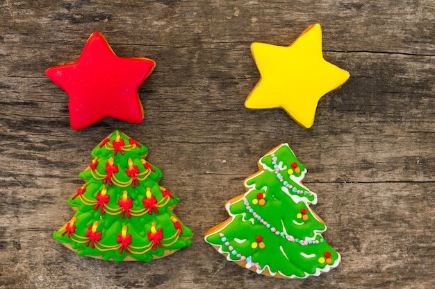 Biscuits de noël festifs en forme d'arbre de noël et d'étoiles. pains d'épice savoureux sur table en bois rustique. vue de dessus