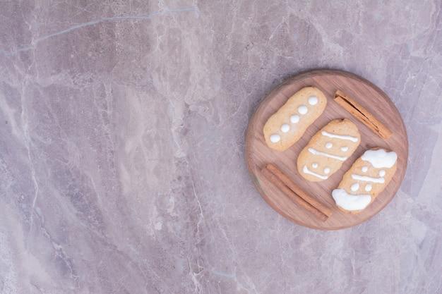 Biscuits de noël en pain d'épice avec des bâtons de cannelle sur planche de bois ronde.