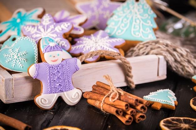 Biscuits de noël en pain d'épice, flocons de neige un gingembre. écharpe tricotée et bâtons de cannelle.
