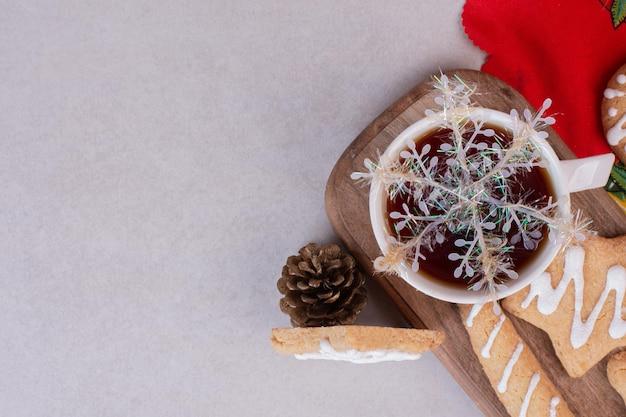 Biscuits de noël avec thé aromatique en tasse sur tableau blanc.
