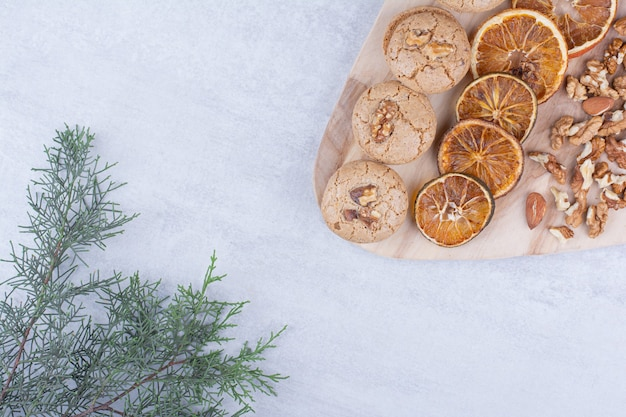 Biscuits, oranges et noix diverses sur planche de bois.
