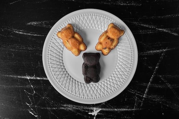 Biscuits ours en peluche dans une assiette blanche.