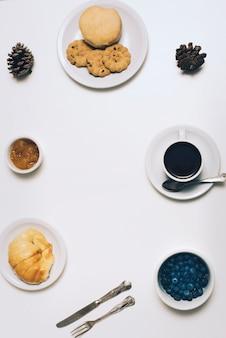 Biscuits; pain; chignon; confiture; pomme de pin; bleuets et tasse à café sur fond blanc