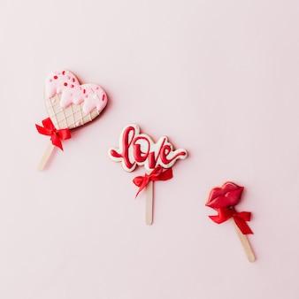 Biscuits en pain d'épice aiment, lèvres, crème glacée au cœur. carte de la saint-valentin. fond rose. photo de haute qualité