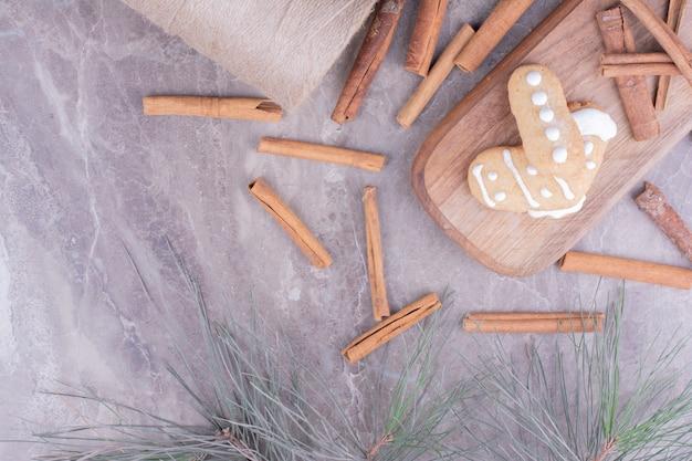 Biscuits de pain d'épice avec des bâtons de cannelle sur une longue planche de bois.