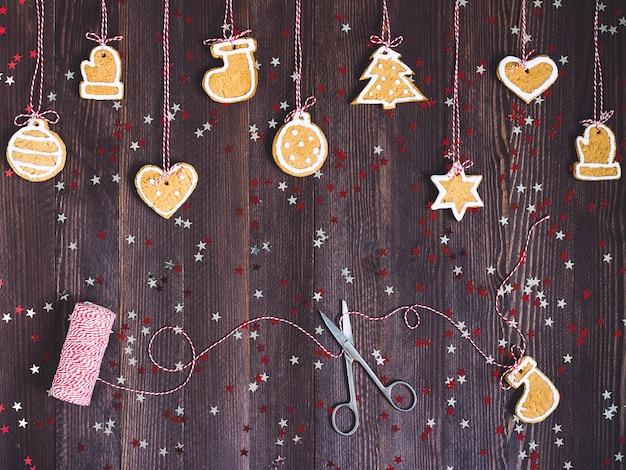 Biscuits pain d'épice sur corde pour la décoration de sapin de noël avec des ciseaux et du fil de nouvel an sur table en bois