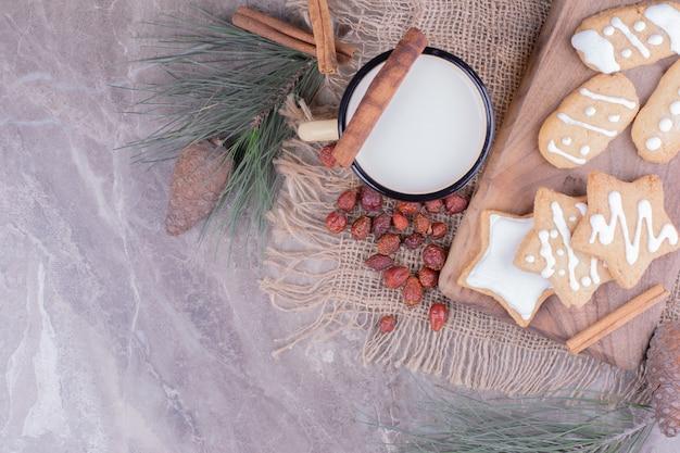 Biscuits de pain d'épice étoile et ovale sur une planche de bois avec de la cannelle et une tasse de lait