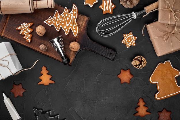 Biscuits de pain d'épice faits maison de noël épices et planche à découper sur fond sombre avec espace de copie f...