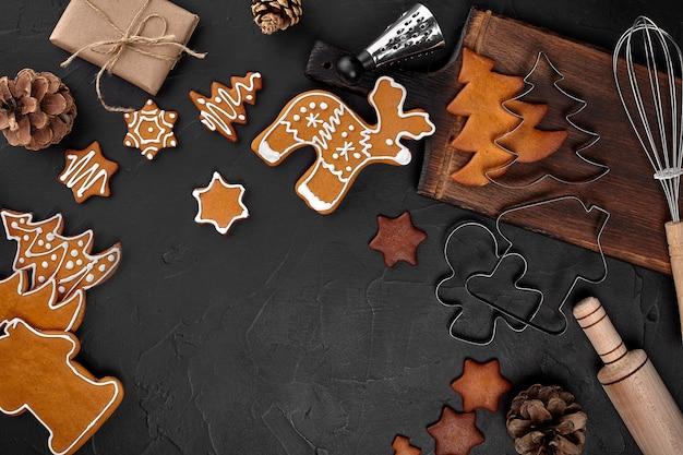 Biscuits de pain d'épice faits maison de noël, épices et planche à découper sur fond sombre avec espace de copie pour la vue de dessus du texte. concept de vacances, de célébration et de cuisine. carte postale de nouvel an et de noël