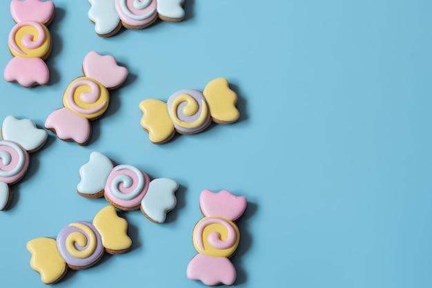Biscuits de pain d'épice festifs colorés sous forme de bonbons recouverts de glaçage sur un espace de copie de fond bleu.
