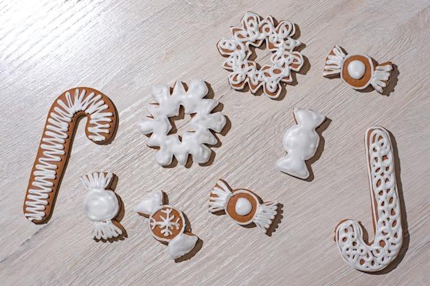 Biscuits de pain d'épice festifs faits à la main sous forme d'étoiles, bonbons, bâtons, arbres de noël. sur un plan de travail léger.