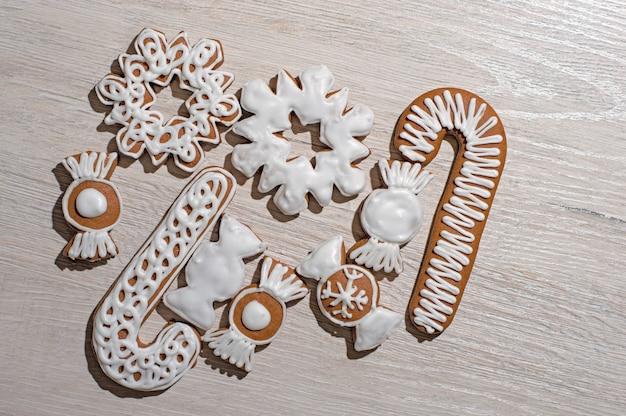 Biscuits de pain d'épice festifs faits à la main sous forme d'étoiles, de bonbons, de bâtons, d'arbres de noël. sur un plan de travail léger.